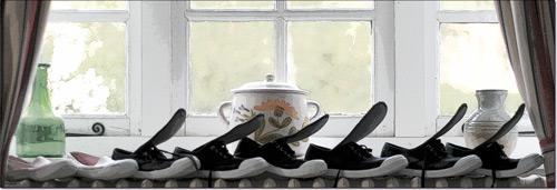 six paires de chaussures séchant sur un radiateur